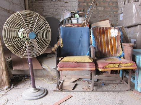 Ein alter Ventilator und zwei langjährig eingesessene Kinostühle warten auf ihre Restauration und die anschliessende Seereise nach Europa.