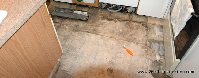 Photo of water damaged kitchen floor before Vesel Construction handled the restoration.