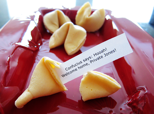 Photograph of a fortune cookie, whose message reads: 'Confucius says: Hooah! Welcome back, Private Jones!' From thestrengthbehindthestrong.com.