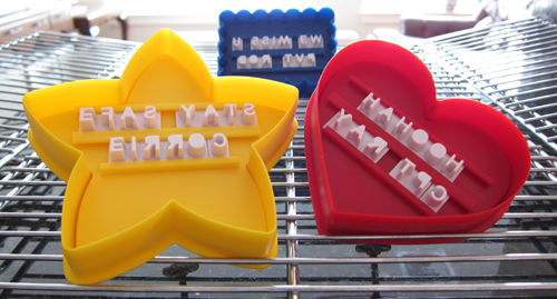 Photographs of cookie cutters with letters inserted (some are backwards or misspell words). From thestrengthbehindthestrong.com.