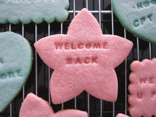 Close-up photograph of a red star shaped cookie reading 'Welcome Back.' From thestrengthbehindthestrong.com.