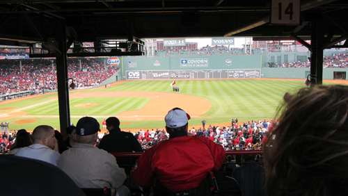Photograph of the view from the Standing Room Only section of Boston's Fenway Park. The entire field is visible, with the first base line running directly in front of the viewer. From thestrengthbehindthestrong.com.