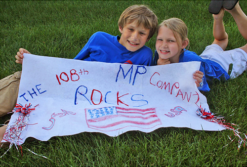 Kids showing off a hand-made poster which reads '108th MP Company Rocks!' From TheStrengthBehindtheStrong.com.