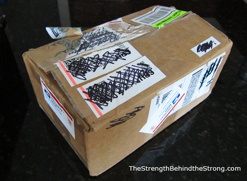 Image of a cardboard box for military care packages covered in crossed-out mailing labels. From TheStrengthBehindtheStrong.com.