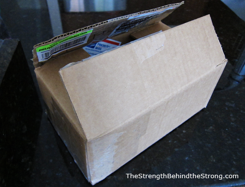 Image of the military care package box taped back together inside-out. Old labels are on the inside, clean cardboard is on the outside. From TheStrengthBehindTheStrong.com.