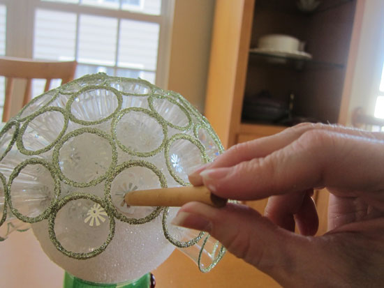Use the dowel or pencil to make sure the pin is pushed in as far as it will  go. Continue to cover the entire Styrofoam ball in this manner, ...