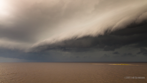 Large shelf cloud over lake waters.
