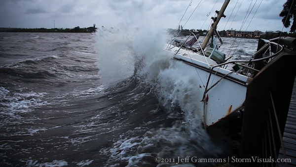 Waves slamming sailboat against rocks and fishing dock