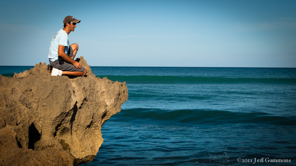 Jeff Gammons taking in the waves and ocean sitting on rocks.