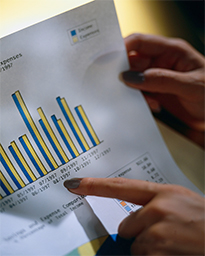 Photo: woman's hand points at a bar chart on a report